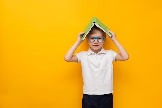 Mignon petit écolier dans des verres tenant un livre sur la tête, copie espace