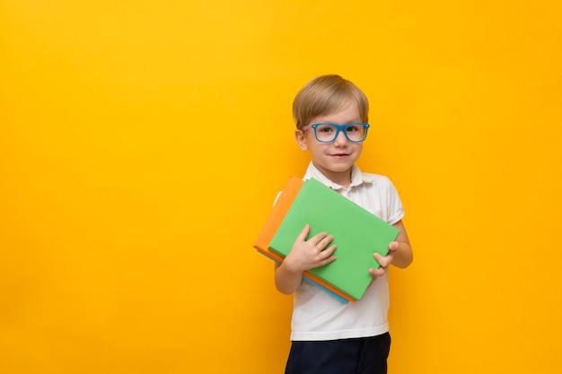 Mignon petit écolier dans des verres tenant des livres sur jaune
