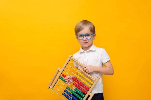 Mignon petit écolier dans des verres tenant des partitions, copiez l'espace. concept mathématique