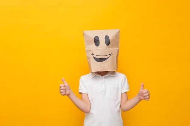 Mignon petit écolier debout avec un sac en papier sur la tête - visage heureux, concept d'émotion hppy
