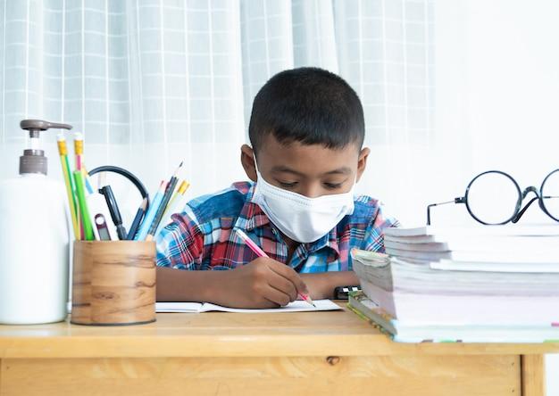 Mignon petit écolier étudie à la maison