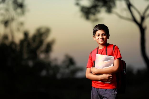 Mignon petit écolier indien avec carnet et sac