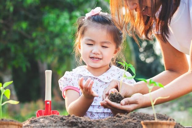 Mignon petit enfant asiatique fille et parent planter ensemble de jeunes plants dans le sol noir