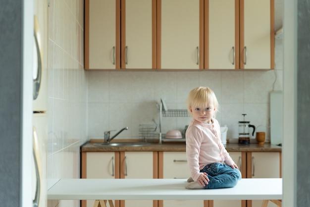 Mignon petit enfant blond assis sur la table dans la cuisine. en attente du petit déjeuner.
