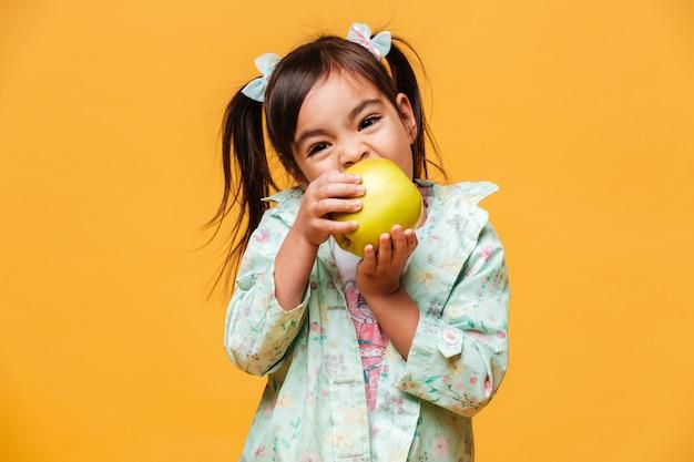 Mignon petit enfant fille mange une pomme.