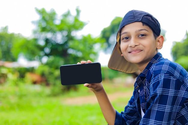Mignon petit enfant indien montrant smartphone avec écran blanc
