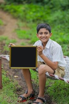 Mignon petit enfant indien montrant le tableau avec copie espace