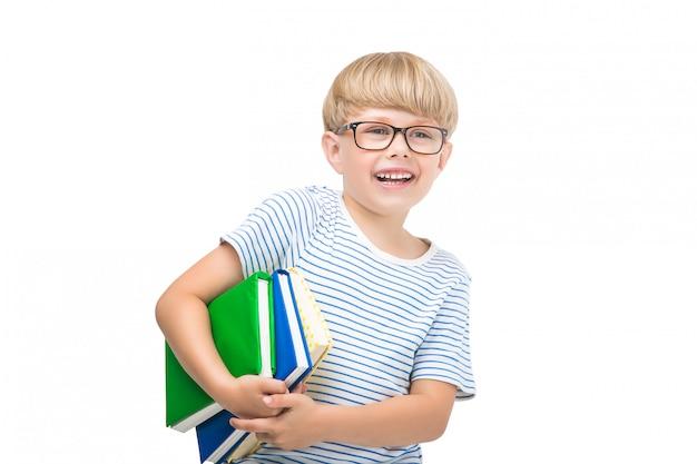 Mignon petit enfant avec des livres et des cahiers adorable enfant lisant. tourné en studio d'écolier. garçon portant des lunettes.