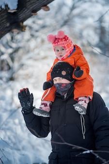 Mignon petit enfant et papa sur une promenade d'hiver enneigée dans la forêt