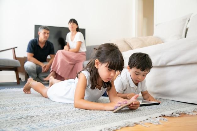Mignon petit frère et sœur utilisant des applications d'apprentissage sur des gadgets, allongé sur le sol pendant que les parents sont assis ensemble
