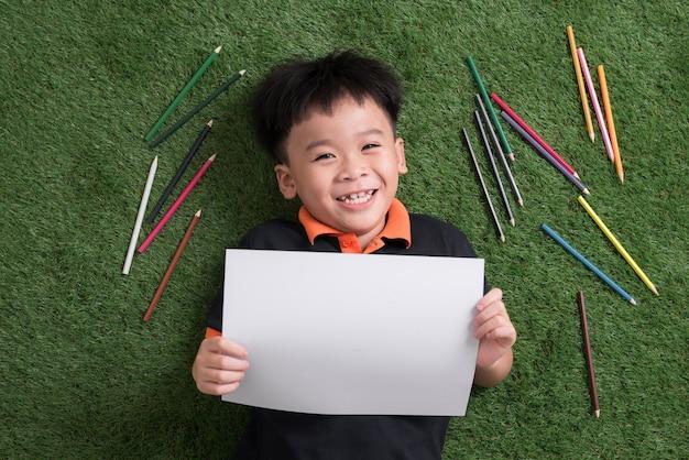 Mignon petit garçon de 7 ans dessin dans un parc à l'extérieur allongé sur l'herbe