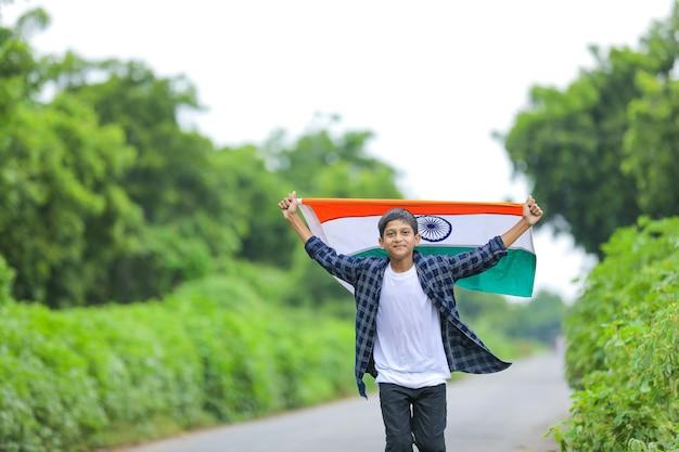 Mignon petit garçon en agitant le drapeau tricolore national indien sur fond de nature