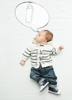 Mignon petit garçon allongé sur le lit et pensant à une bouteille de lait