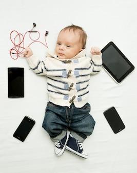 Mignon petit garçon allongé sur le lit avec des tablettes numériques et des smartphones