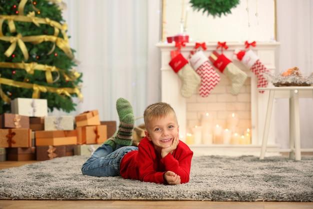 Mignon petit garçon allongé sur un tapis à la maison