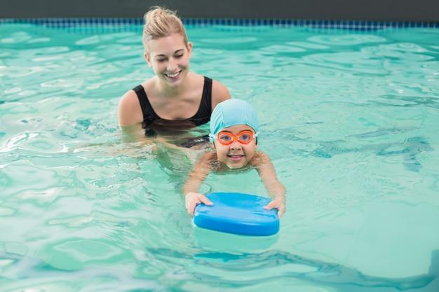 Mignon petit garçon apprend à nager avec l'entraîneur