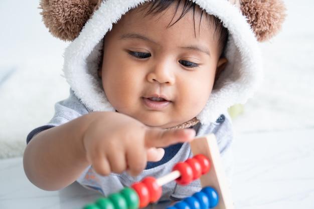 Mignon petit garçon asin jouant avec un jouet en bois