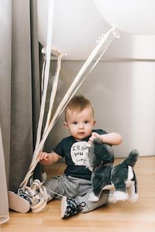 Mignon petit garçon assis avec de gros ballons blancs, enfance heureuse, jeux pour enfants