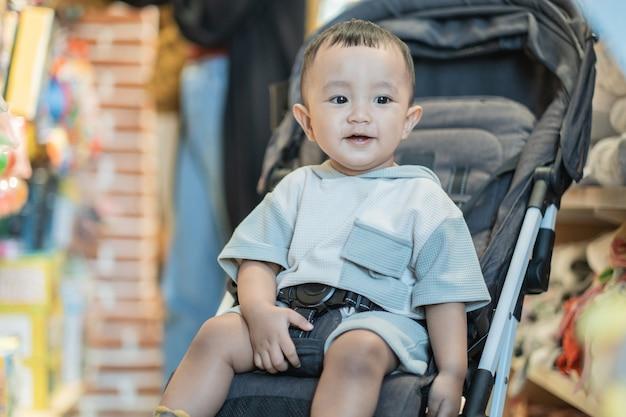 Mignon petit garçon assis sur une poussette dans le centre commercial