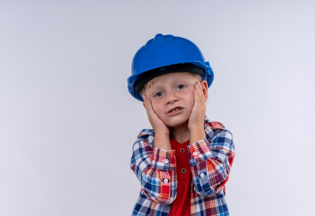 Un mignon petit garçon aux cheveux blonds portant chemise à carreaux en casque bleu en gardant les mains sur le visage sur un mur blanc