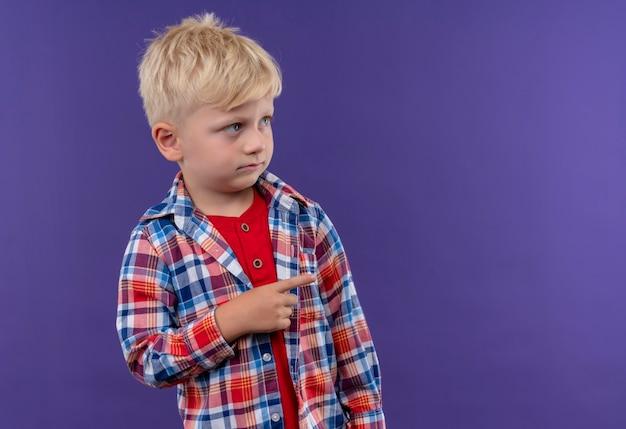 Un mignon petit garçon aux cheveux blonds portant chemise à carreaux pointant avec l'index sur quelque chose sur un mur violet