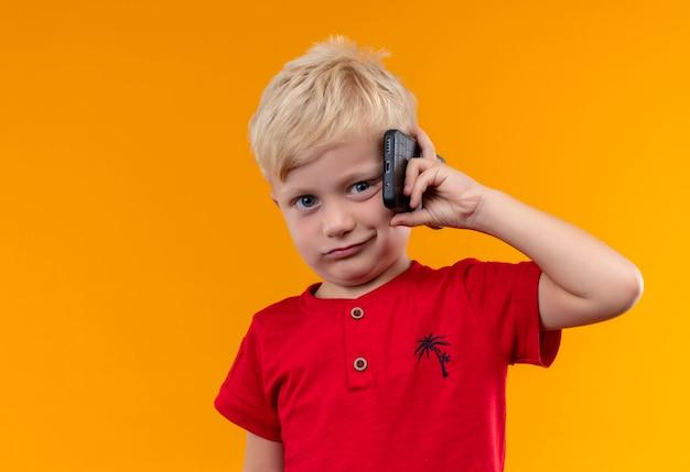 Un mignon petit garçon aux cheveux blonds portant une chemise rouge tenant un téléphone mobile tout en regardant sur un mur orange