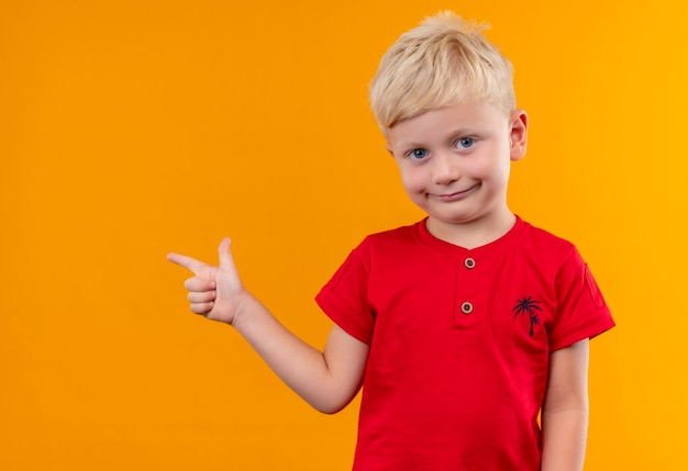 Un mignon petit garçon aux cheveux blonds portant un t-shirt rouge montrant quelque chose avec l'index à la recherche sur un mur jaune