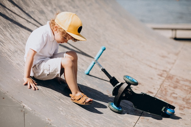 Mignon petit garçon aux cheveux bouclés équitation scooter