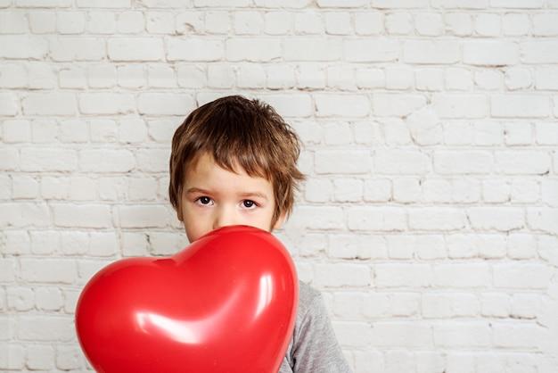 Mignon petit garçon avec ballon en forme de coeur rouge sur fond de mur de briques blanches, fond de saint valentin