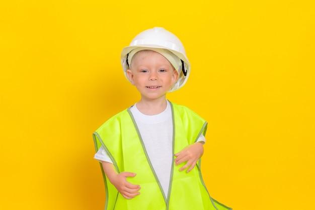 Un mignon petit garçon blanc, vêtu d'un gilet réfléchissant et d'un casque blanc, se tient sur un mur jaune.