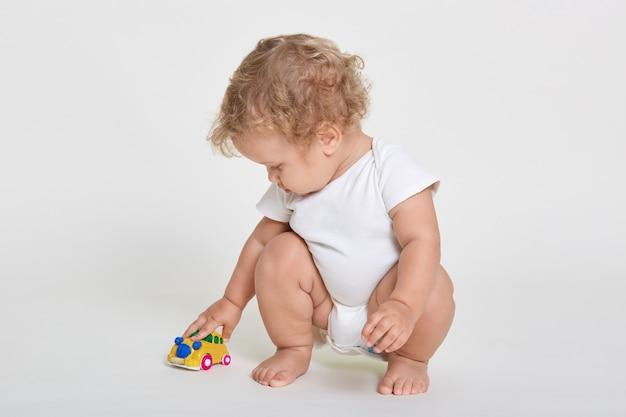 Mignon petit garçon blond aux cheveux bouclés habille le costume de corps jouant avec une voiture jouet de couleur assis pieds nus contre l'espace blanc