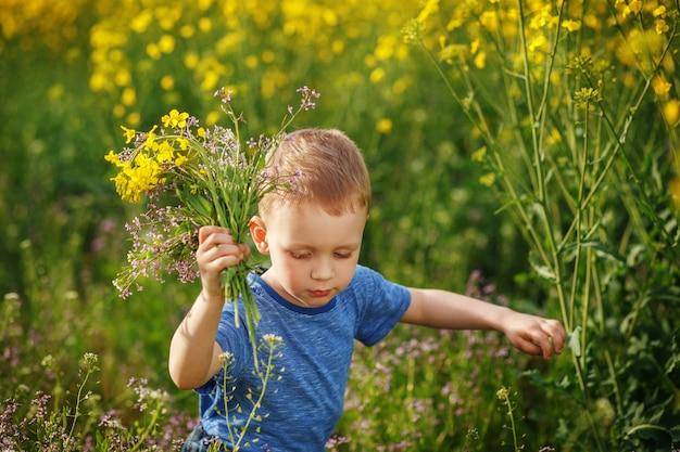 Mignon petit garçon blond en cours d'exécution avec un bouquet de fleurs sur un pré jaune