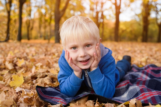 Mignon petit garçon blond se trouve sur un plaid en feuilles d'automne jaune