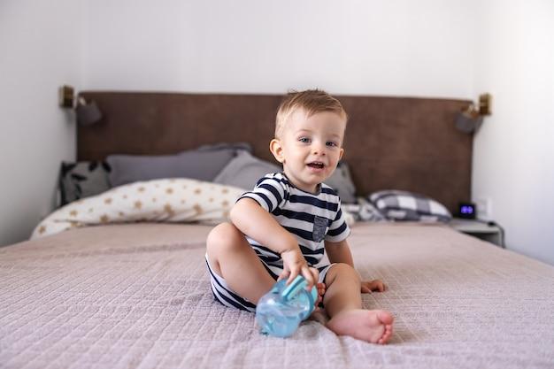 Mignon petit garçon blond souriant et regardant la caméra avec ses beaux yeux bleus assis sur le lit dans la chambre et tenant sa bouteille avec de l'eau.