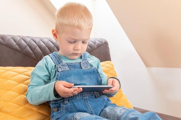 Mignon petit garçon blond tenant un smartphone et regarder des dessins animés