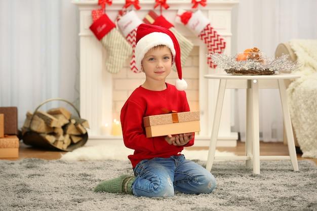 Mignon petit garçon en bonnet de noel avec cadeau de noël à la maison