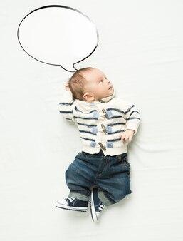 Mignon petit garçon avec bulle de dialogue allongé sur le lit