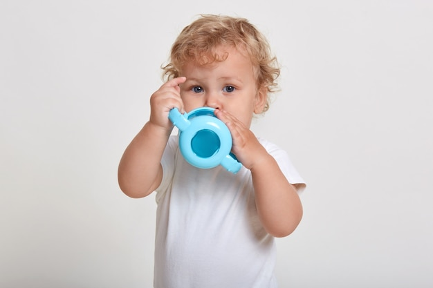 Mignon petit garçon buvant à la bouteille, enfant de sexe masculin portant un t-shirt, a les cheveux blonds ondulés