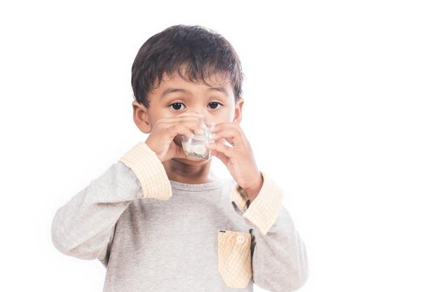 Mignon petit garçon buvant du lait