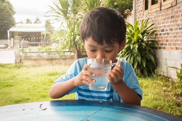 Mignon petit garçon buvant de l'eau dans le parc
