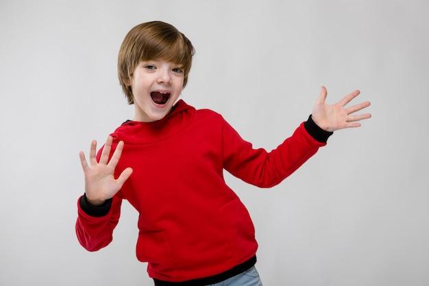 Mignon petit garçon caucasien confiant en pull rouge montrant la paume ouverte avec la bouche ouverte