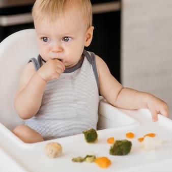 Mignon petit garçon en chaise haute, manger des légumes