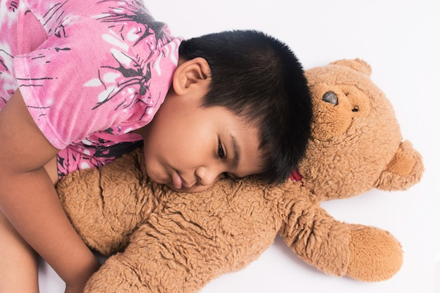 Mignon petit garçon couché sur le sol avec ours en peluche brun
