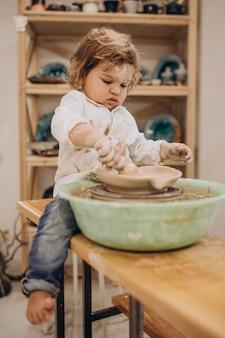 Mignon petit garçon à un cours de poterie
