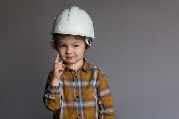 Mignon petit garçon dans un casque, bâtiment et concept architectural