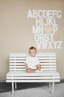 Un mignon petit garçon dans une chemise blanche assis sur le banc blanc à l'intérieur devant le mur avec l'alphabet
