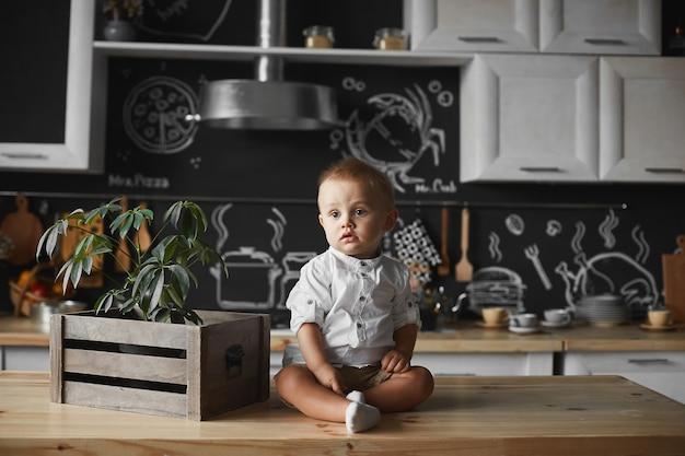 Mignon petit garçon dans une chemise blanche et un short à la recherche de côté alors qu'il était assis sur la table de la cuisine