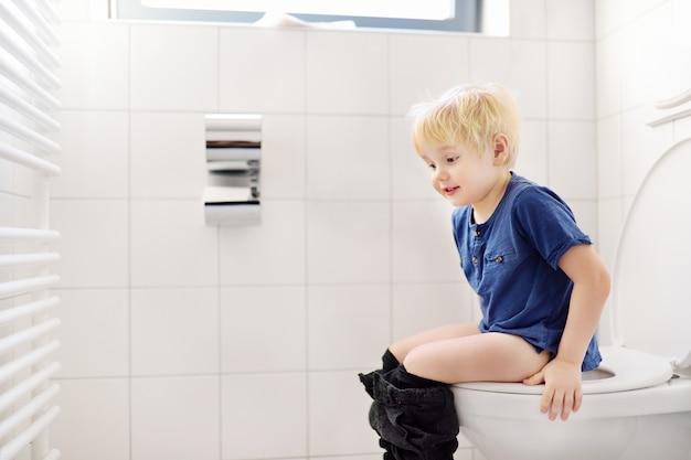 Mignon petit garçon dans les toilettes