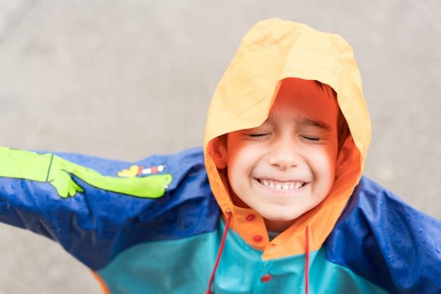 Mignon petit garçon dehors pour goûter la pluie