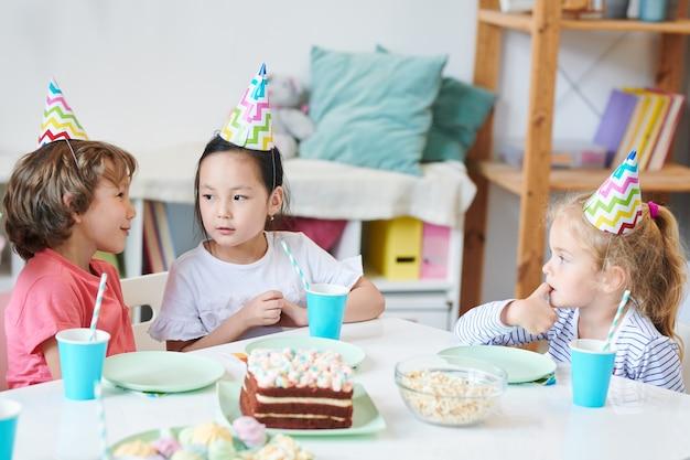 Mignon petit garçon disant quelque chose à jolie fille asiatique en chapeau d'anniversaire par table de fête tout en prenant des boissons et des desserts